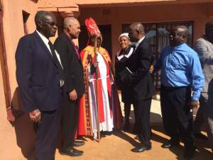 Jake Dikobo (center) speaks with the bishops after worship on Sunday.